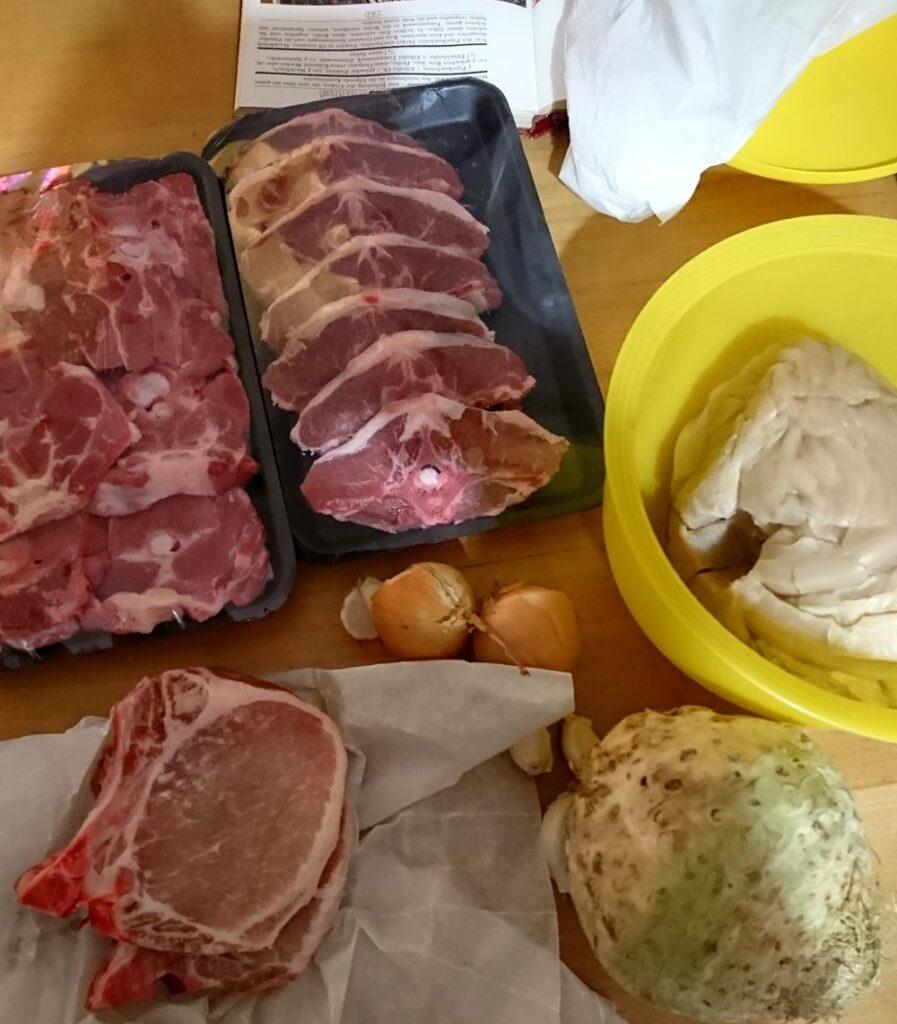 Zutatensammlung Podvaraik, zwei Schweinekoteletts, jeweils ein knappes Kilo Lammhals und -steak, ein Sauerkohl un Schüssel, zwei Zwiebeln, einige Knoblauchzehen. Auch auf dem Foto, aber im Rezept doch nicht verwendet: ein Knollensellerie.